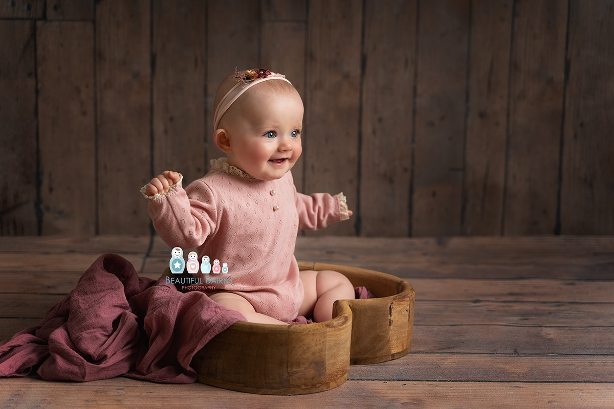 professional baby portrait of baby sitting in a heart bowl on a wooden backdrop smiling off camera wearing a pink sleeved outfit and headband. By edinburgh baby photographer Beautiful Bairns Photography