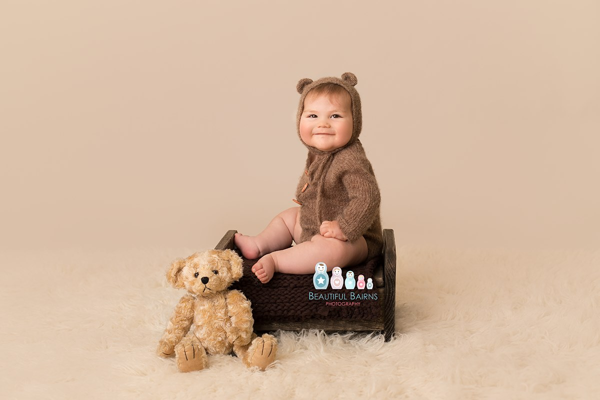 professional baby portrait photo of baby boy in teddy bear outfit sat on wooden bench with teddy bear by baby photographer Beautiful Bairns Photography