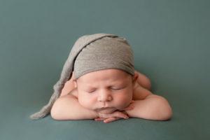 professional newborn baby photo of baby boy laid on tummy wearing grey sleepy hat on green blanket by edinburgh newborn photographer beautiful bairns photography