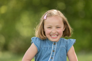 professional photograph of a girl smiling wearing a blue dress in front of a blurry green outdoor backdrop by professional kids photographer Beautiful Bairns Photography Edinburgh