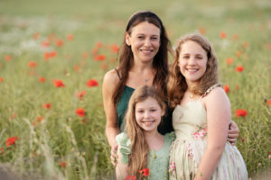 professional family portrait of mum and two daughters embracing in a poppy field outside of Edinburgh by professional family photographer Beautiful Bairns Photography