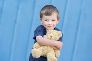 professional kids photo of a boy cuddling a teddy bear smiling in front of a blue backdrop. Professional outdoor kids photos by kids photographer Beautiful Bairns Photography Edinburgh