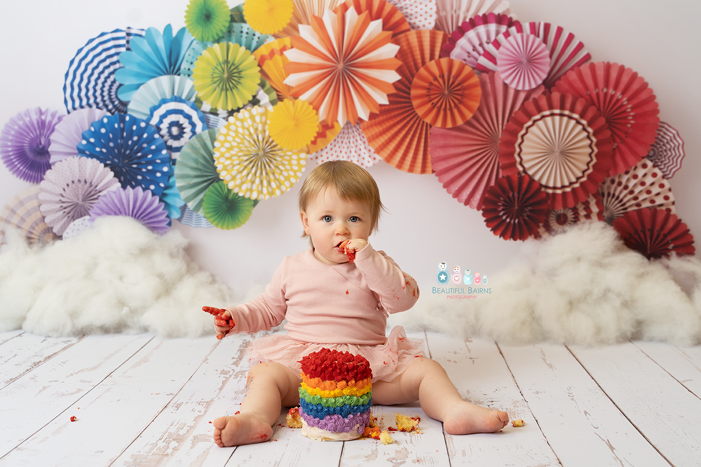 cake smash photo of little girl celebrating 1st birthday with a rainbow themed cake smash with rainbow cake and rainbow paper fans behind her by cake smash photographer beautiful bairns photography edinburgh