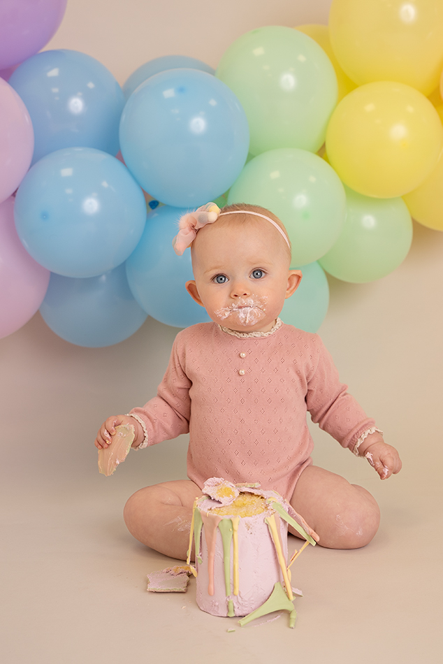 photo of baby having a rainbow themed cake smash photoshoot with rainbow coloured balloon garland and rainbow cake by Edinburgh baby photographer Beautiful Bairns Photography