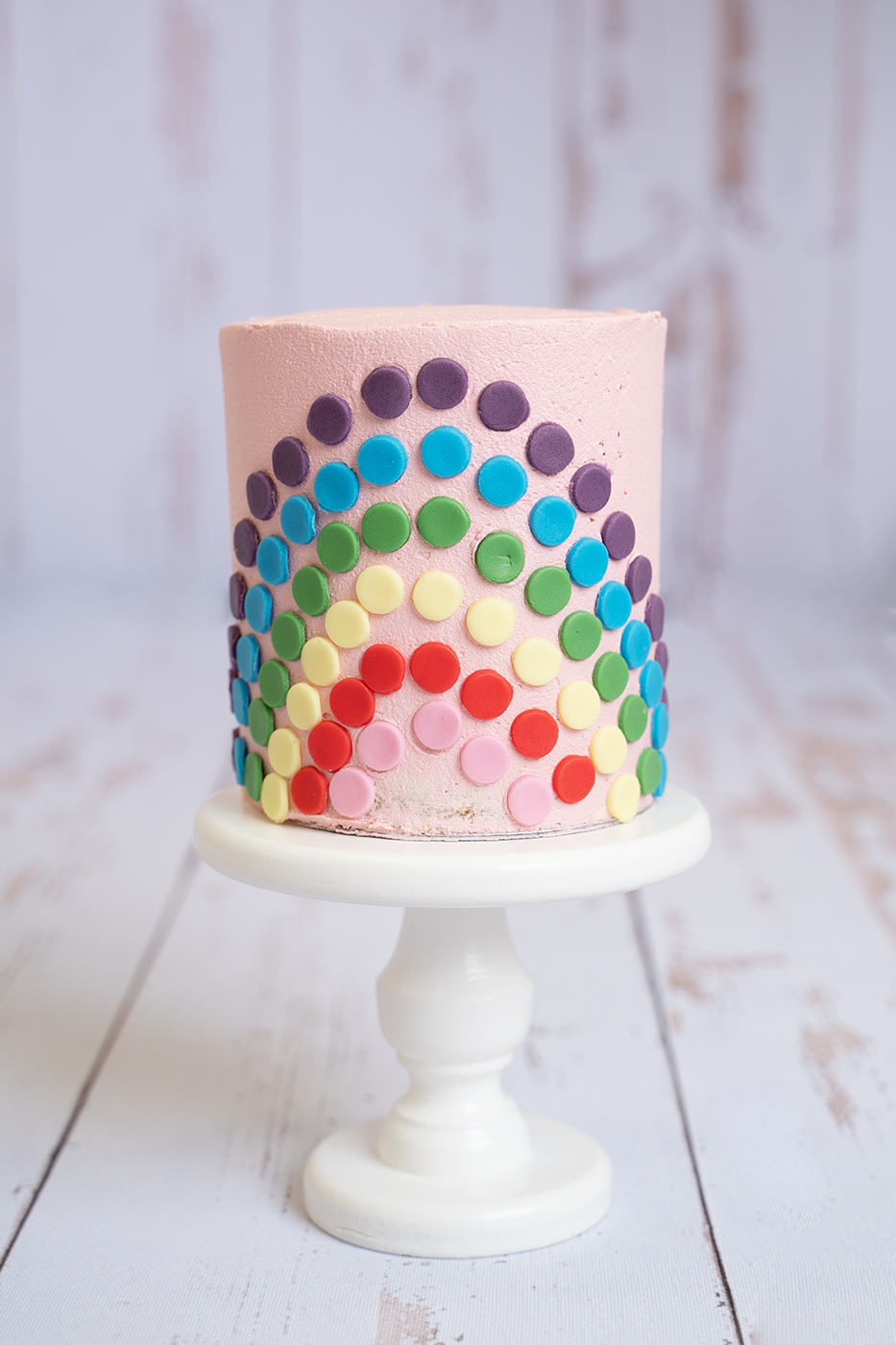 professional photo of a cake smash cake featuring pink icing and rainbow on front by cake smash photographer Edinburgh Beautiful Bairns Photography