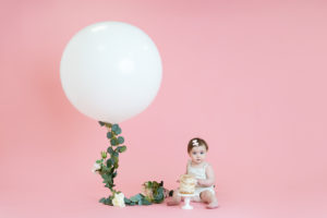 professional cake smash photo of baby girl sitting with a cake and large white balloon on pink backdrop by cake smash photographer Beautiful Bairns photography Edinburgh